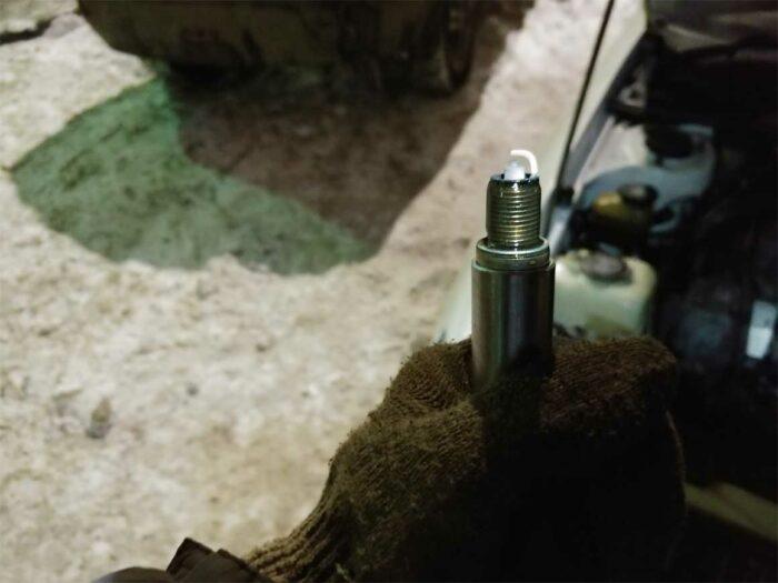Фотография демонтированной свечи зажигания, цвет электродов - белый, означает бедную смесь.