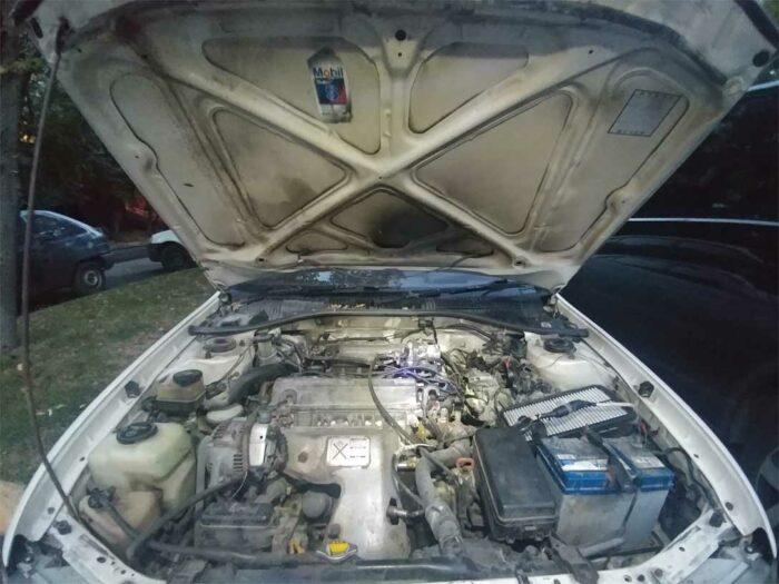 На фотографии подкапотное пространство сгоревшей Toyota Corona Копоть.