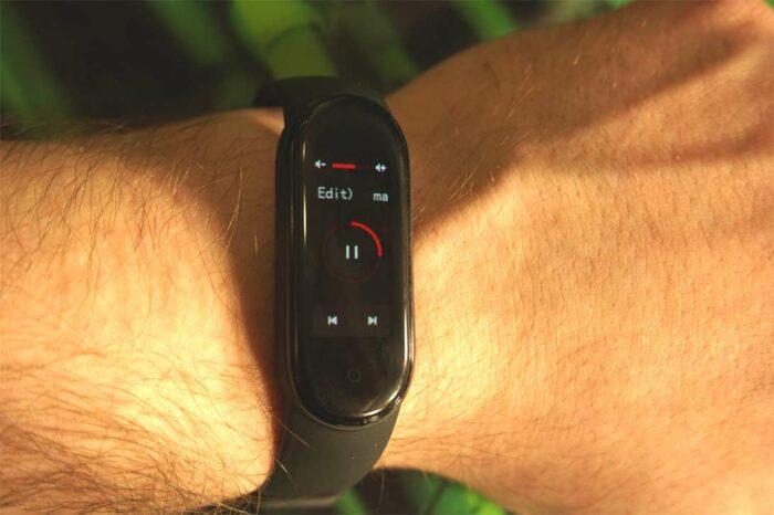 Умный фитнес-браслет Xiaomi Mi Band 5 - дистанционное управление музыкой, на фото видно, что кнопки переключения треков очень маленькие.